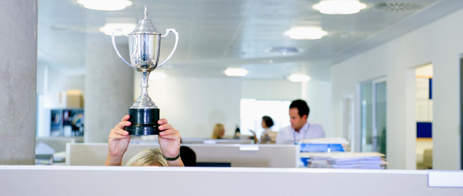 Person h?lt Pokal über dem Kopf hinter Abtrennung einer Bürokabine im Gro?raumbüro  25597641
