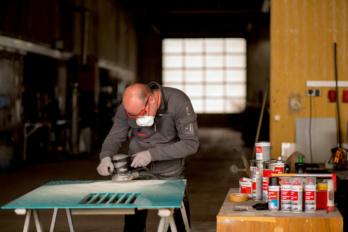Abschleifen einer Lackschicht mit Exzenterschleifer für Vorbereitung der Reparaturlackierung